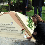 "Photo: UNODC staff member puts a flower at the ""Tree of Hope"" monument in remembrance of those affected by drug addiction"
